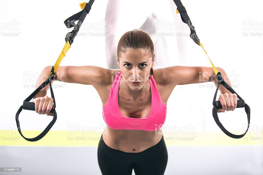 Woman working out on suspension equipment stock photo
