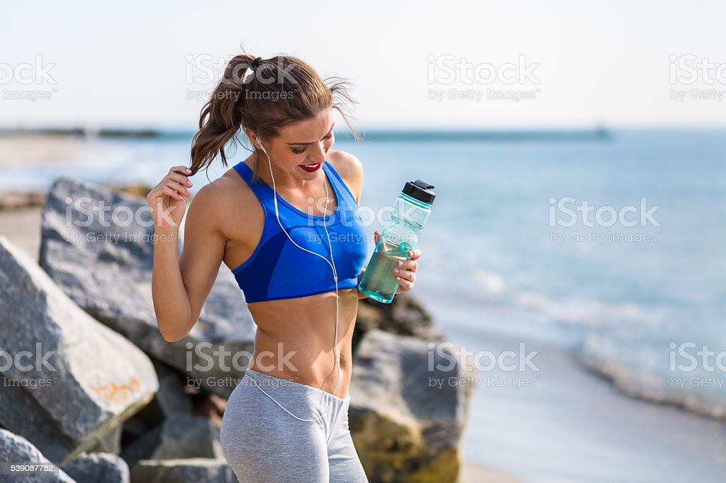 Woman working out outdoors in the summer at the beach stock photo
