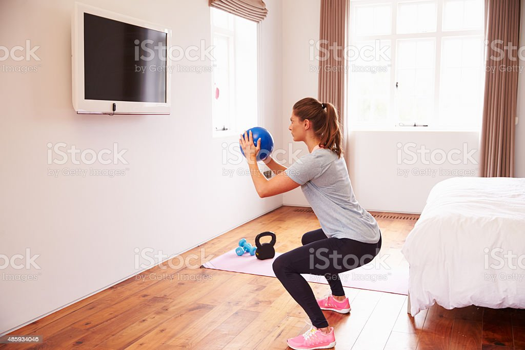 Woman Working Out To Fitness DVD On TV In Bedroom stock photo