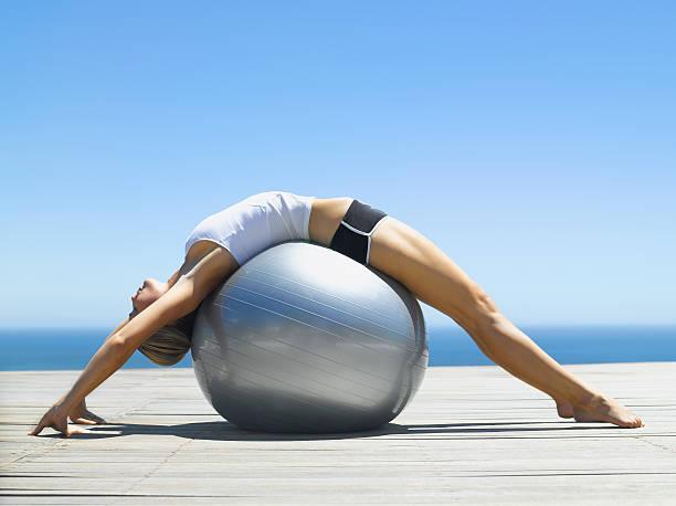 donna che lavora con una palla di esercizio - metodo pilates foto e immagini stock