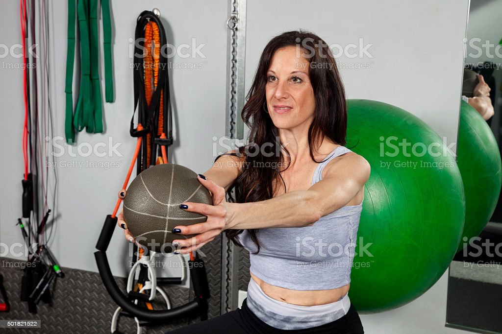 Woman working out with balls, holding weight ball straight out stock photo