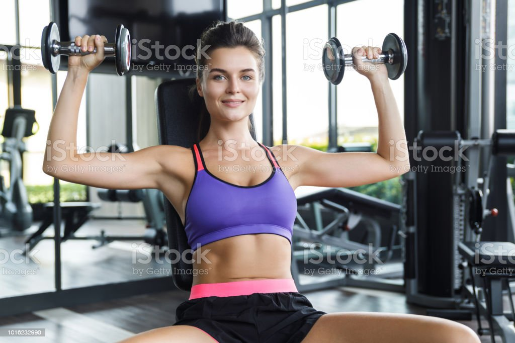 Woman working out with dumbbells in gym. Shoulder press. stock photo