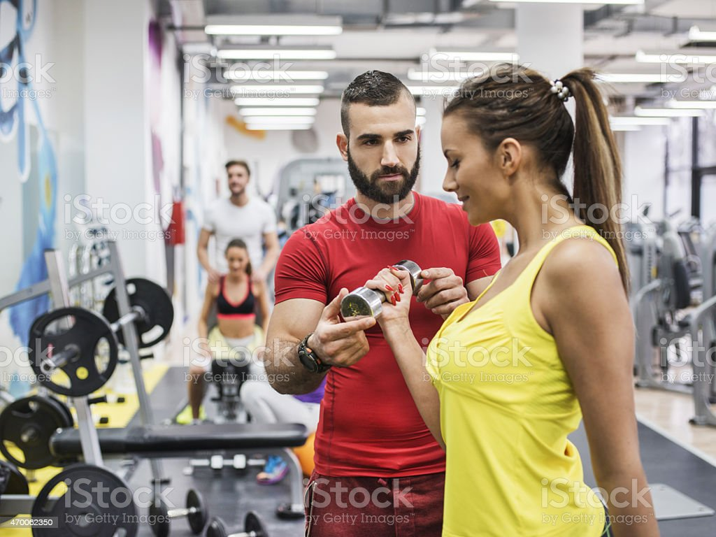 Woman working out with personal trainer in a gym. stock photo