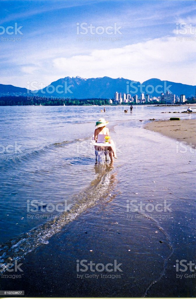 Woman working outdoors at desk on beach stock photo