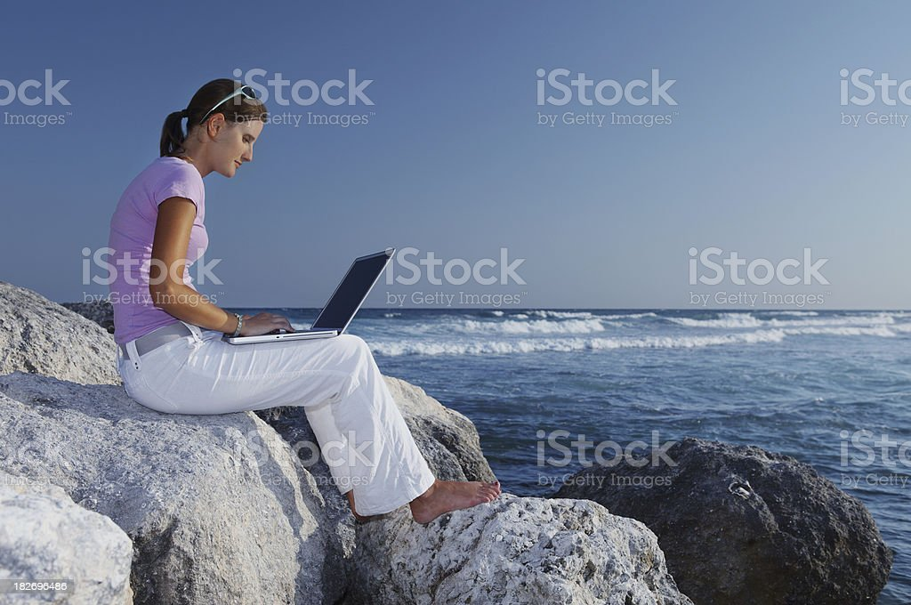 Woman working outdoors on the beach with laptop royalty-free stock photo