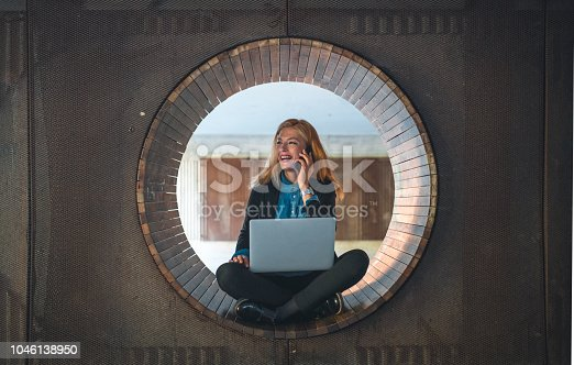 Young woman sitting on a bench and she is using laptop computer. She is taling on mobile phone, she is happy and she is smiling.