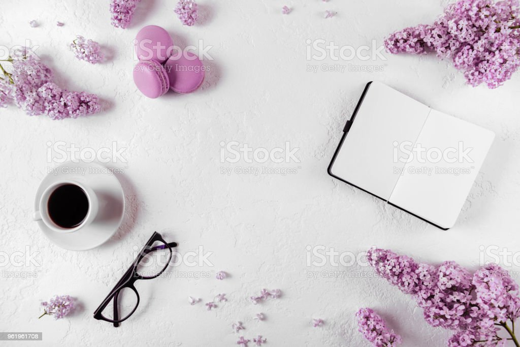 Coffee, macaron, clean notebook, eyeglasses and flower on white table...