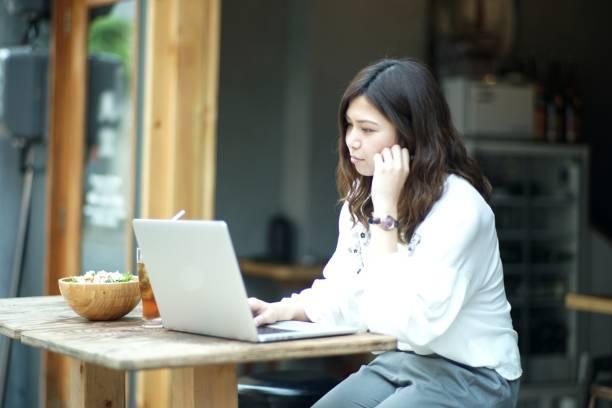 女性バーでノート パソコンでの作業 - 大学生 パソコン 日本 ストックフォトと画像