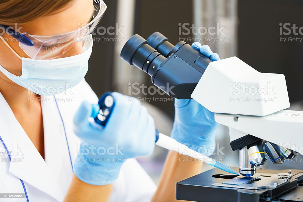 Woman working with a microscope. stock photo