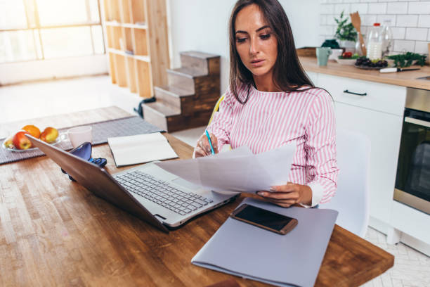 Woman working with documents and laptop in the kitchen at home stock photo