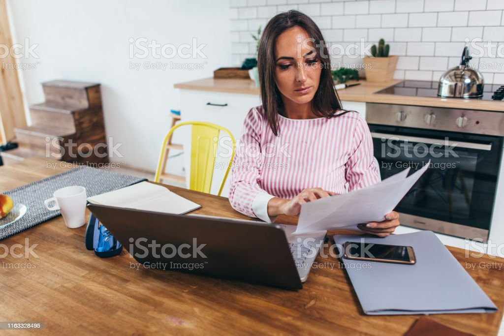 Woman working with documents and laptop in the kitchen at home Woman working with documents and laptop in the kitchen at home. Accountancy Stock Photo