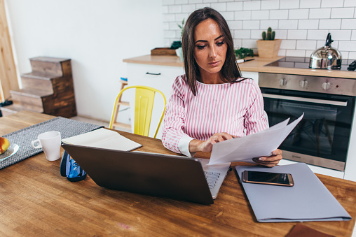 Woman Working With Documents And Laptop In The Kitchen At Home Stock Photo - Download Image Now