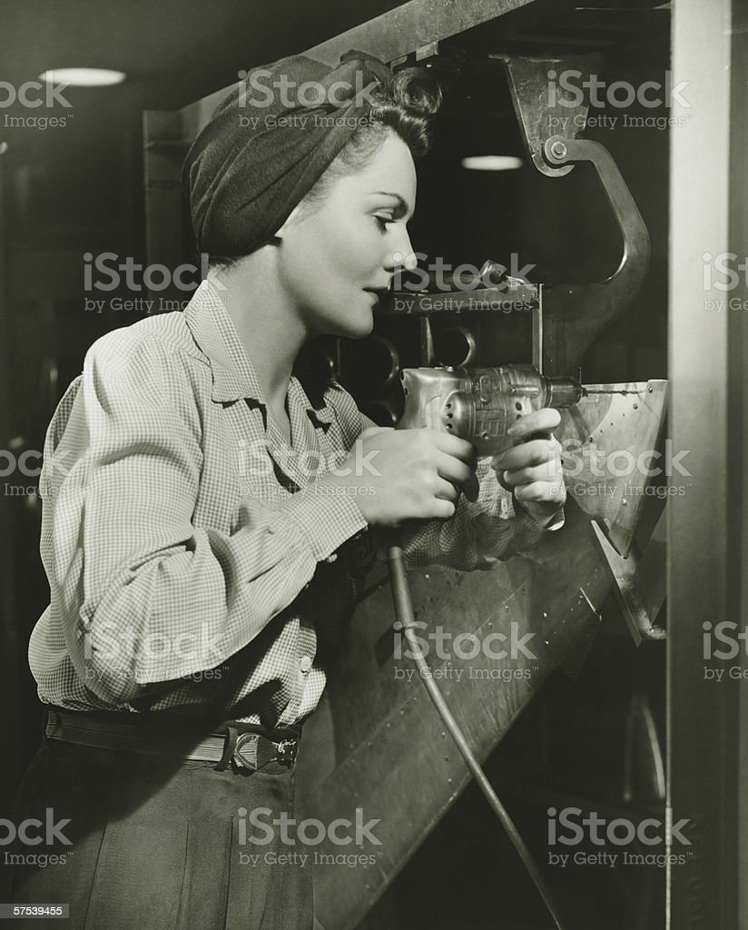 Woman working with electric drill in factory, (B&W) stock photo