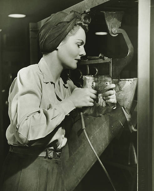woman working with electric drill in factory, (b&w) - world war ii stock photos and pictures