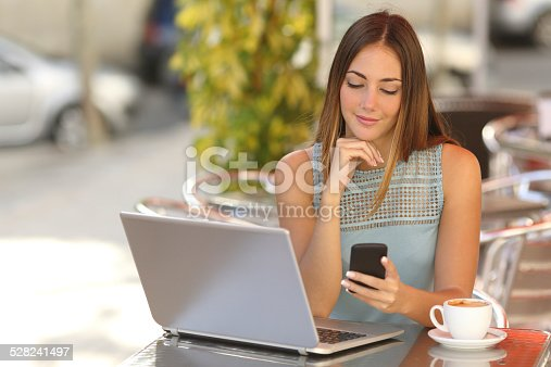 istock Woman working with her phone and laptop in a restaurant 528241497