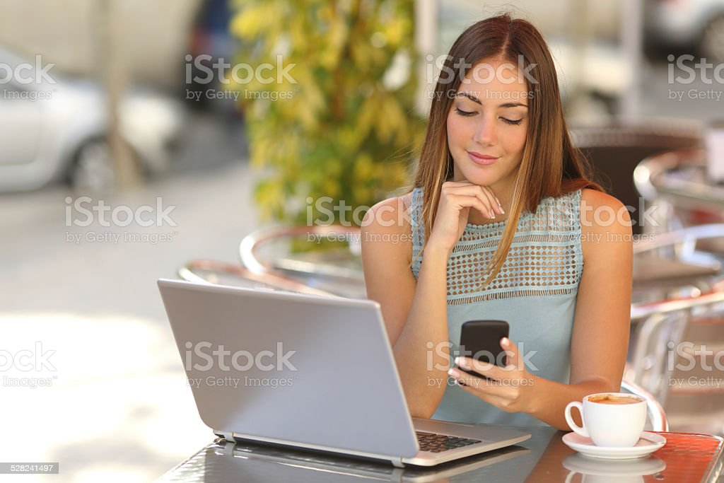 Woman working with her phone and laptop in a restaurant stock photo