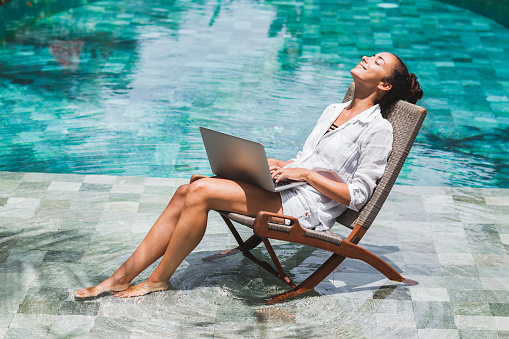 Woman working with laptop by the pool. Freelance work in tropical country