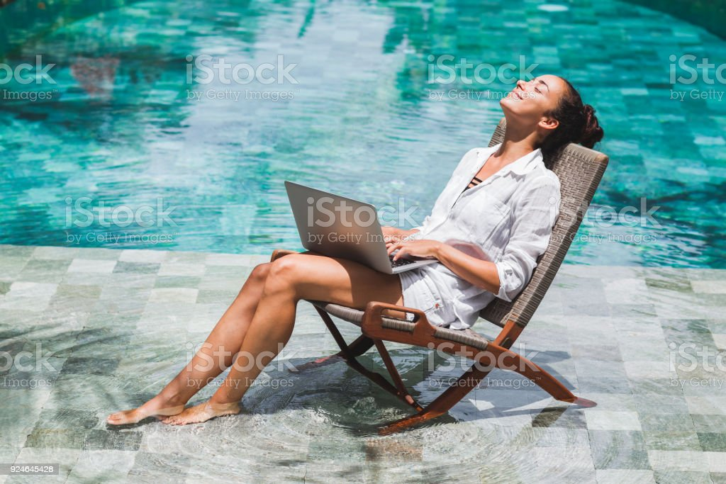 Woman working with laptop by the pool. Freelance work in tropical country stock photo