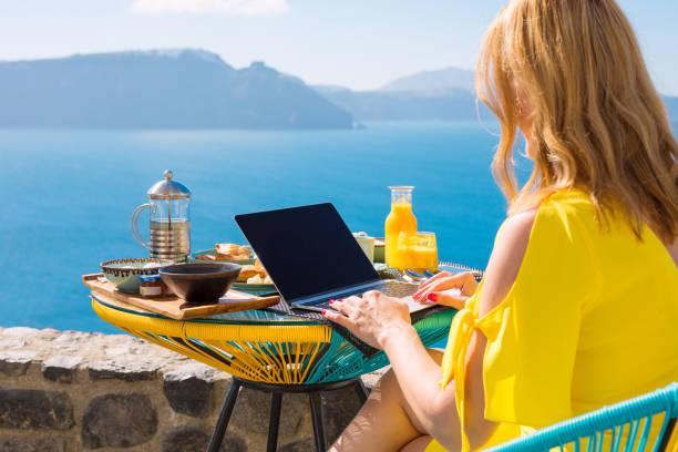 frau mit laptop beim frühstück - reiseblogger stock-fotos und bilder