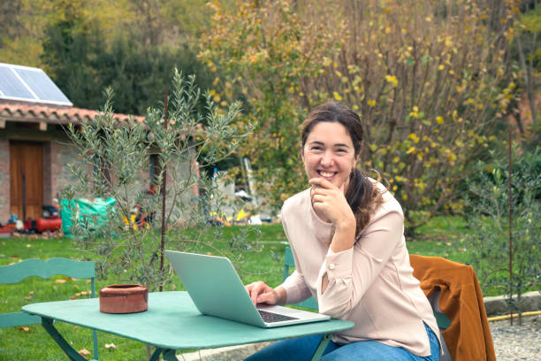 Woman working with laptop in the garden stock photo