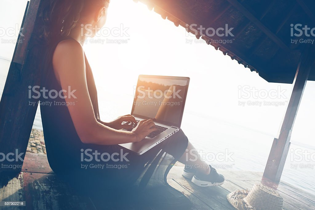 Woman working with laptop on the beach stock photo