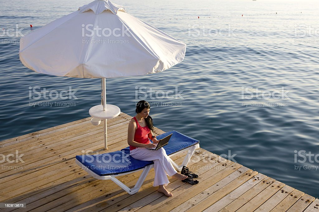 Woman working with laptop on vacation in the bach royalty-free stock photo
