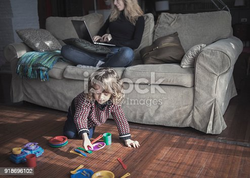 istock Woman working with laptop while child is playing with toys at home 918696102