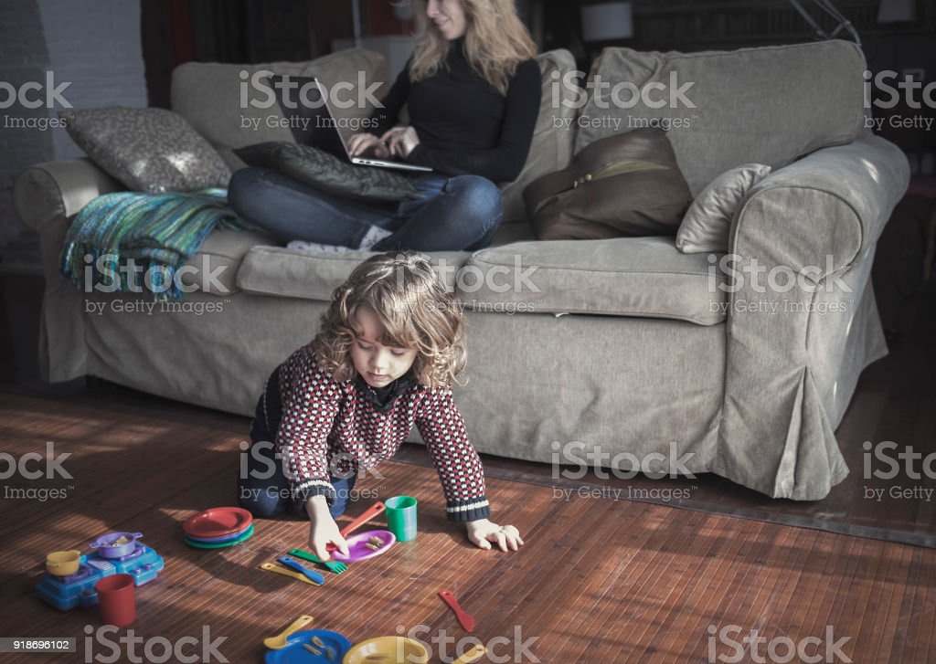 Woman working with laptop while child is playing with toys at home stock photo