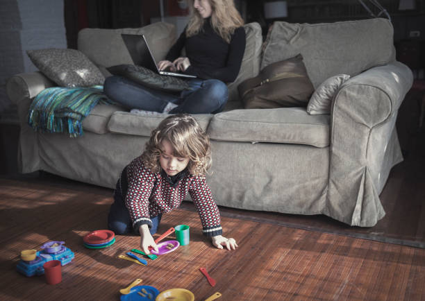 Woman working with laptop while child is playing with toys at home Woman working with laptop while child is playing with toys at home ignoring stock pictures, royalty-free photos & images