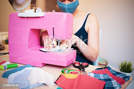 Woman working with sewing machine making trendy face medical mask for preventing and stop coronavirus spreading - Homemade manufacturing concept - Reuse of used clothes - Main focus on hands