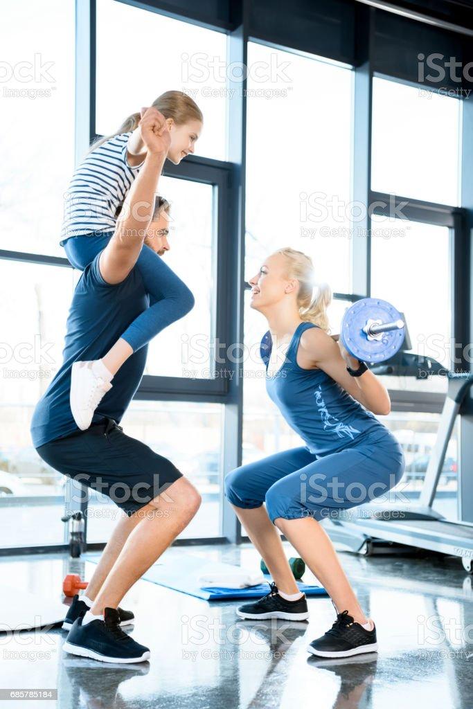 Kadın egzersiz halter adam kızı ile onun omuzlarında eğlenmek ile royalty-free stock photo