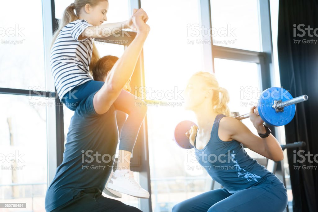 Woman workout with barbell while man having fun with daughter on his shoulders royalty-free stock photo
