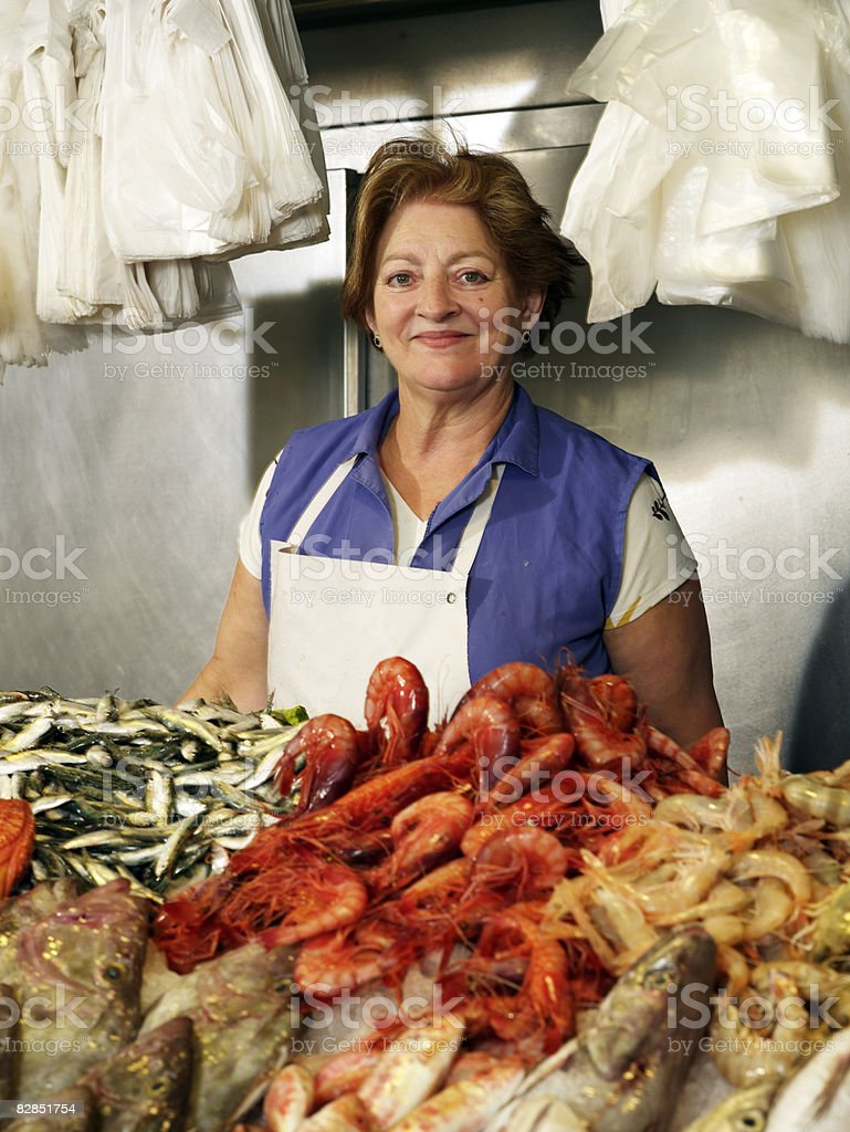 Woman works at fish stall royaltyfri bildbanksbilder