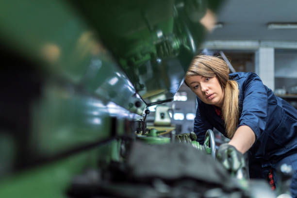 Woman works on an internal grinding machine. Stage of metal finishing of parts Photo of young brown hair woman in blue uniform wearing Protective Gloves at metallurgy factory. Beauty professional factory female employee using industrial machine to milling components. Beautiful Caucasian woman as industrial worker at metal sheet profiling machine at manufacturing factory. metal worker stock pictures, royalty-free photos & images