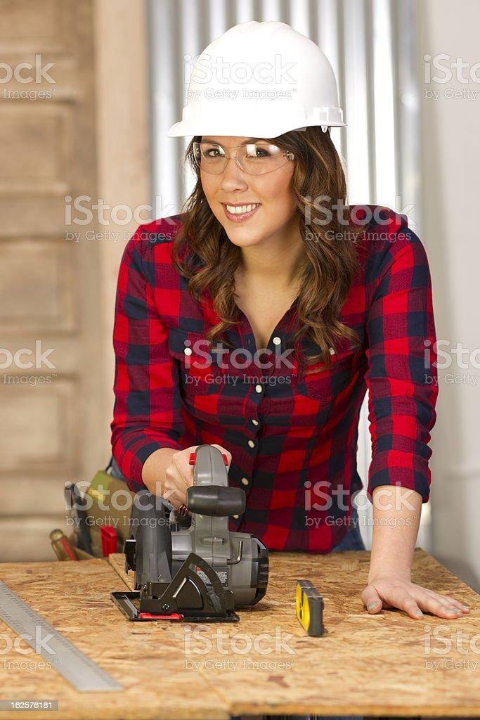 Woman Works on Bench Cutting Board Circular Saw royalty-free stock photo