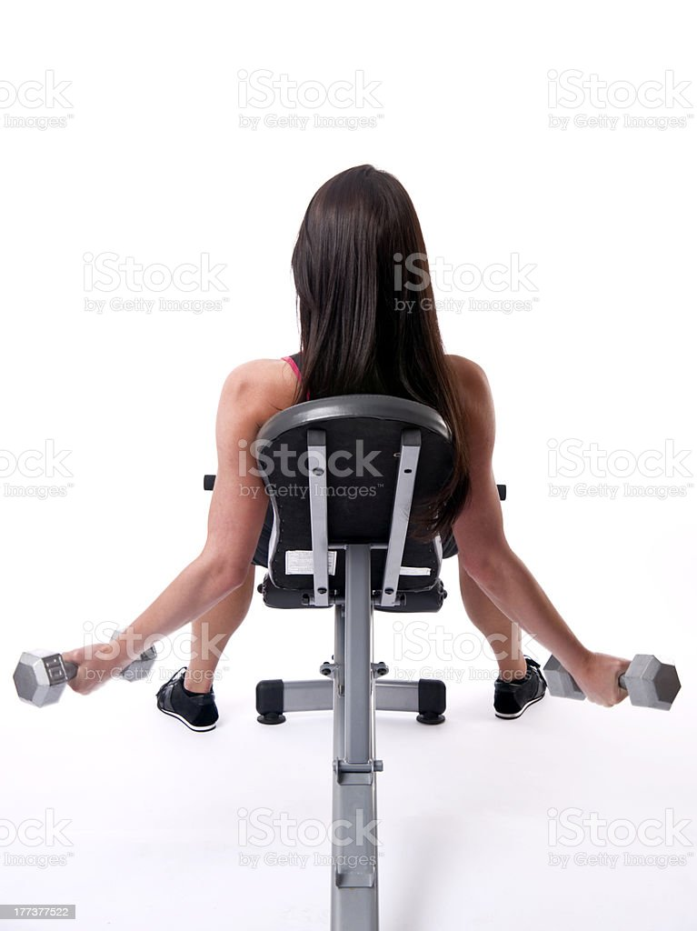 Woman Works Out Curling Barbells on Weight Bench royalty-free stock photo