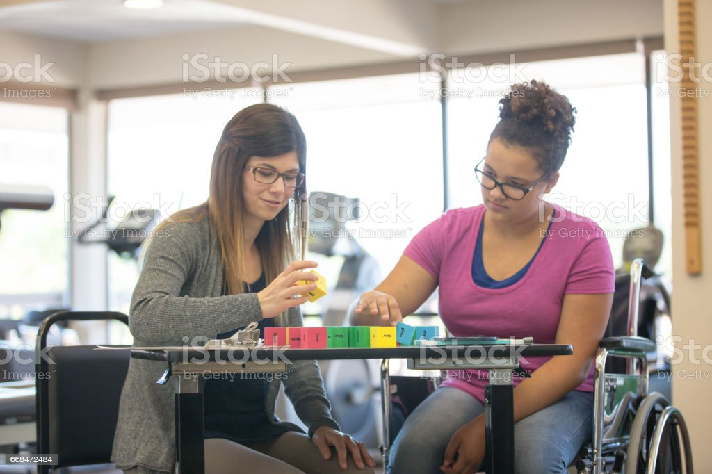 Woman works with teenage girl at rehab clinic stock photo