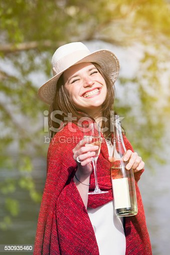 873264516istockphoto woman wrapped in a red blanket holding a bottle champagne 530935460
