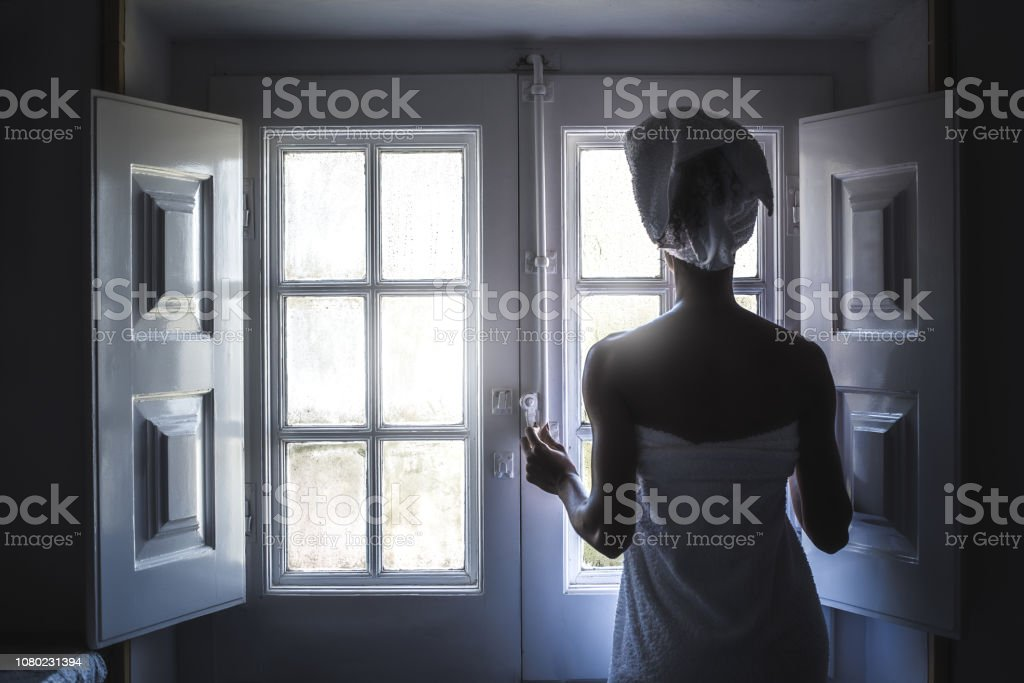 Woman wrapped in a towel looking by a vintage window. stock photo
