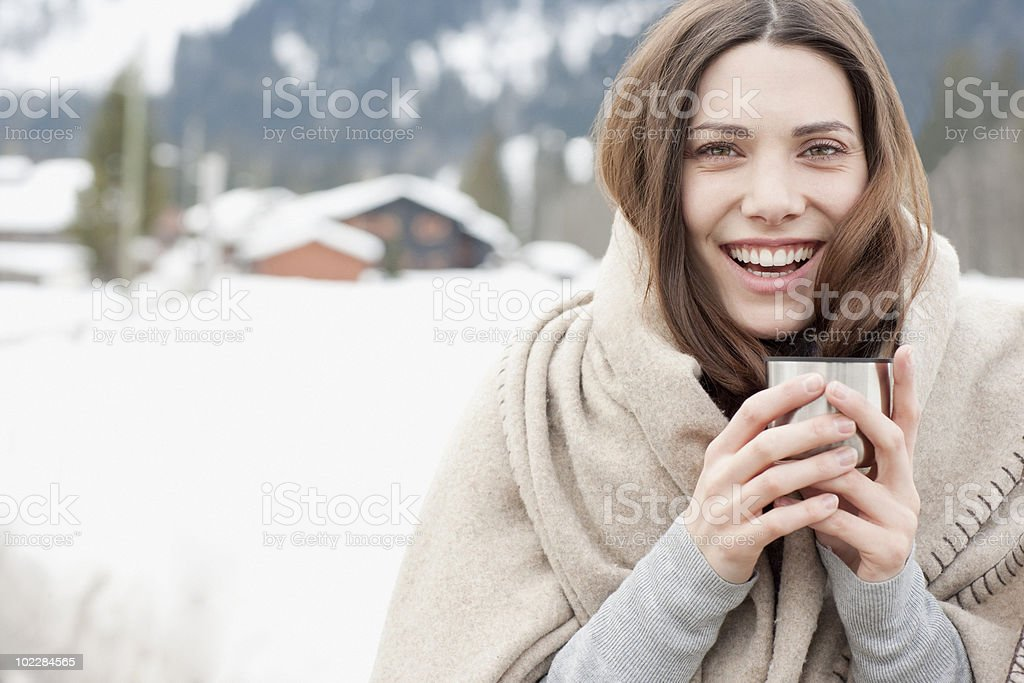 Woman wrapped in blanket drinking coffee stock photo