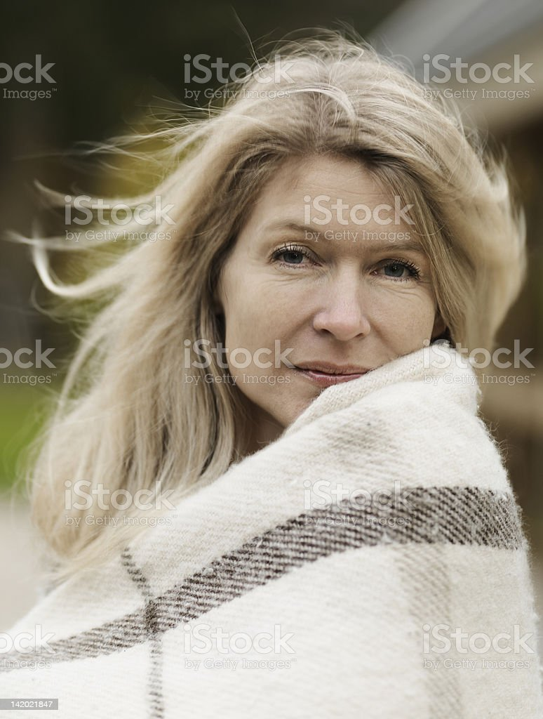 Woman wrapped in blanket outdoors stock photo