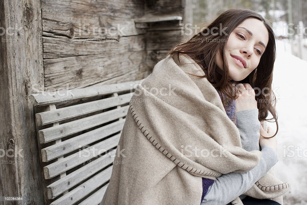 Woman wrapped in blanket sitting on bench stock photo