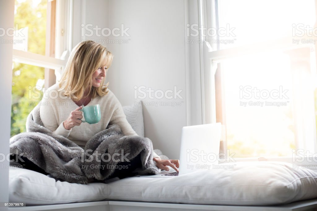 Mature woman holding coffee cup while working on laptop. Smiling...