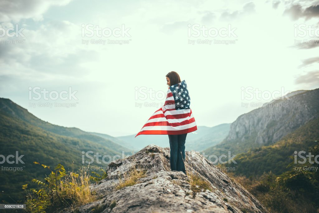 Woman wrapped in US flag stock photo