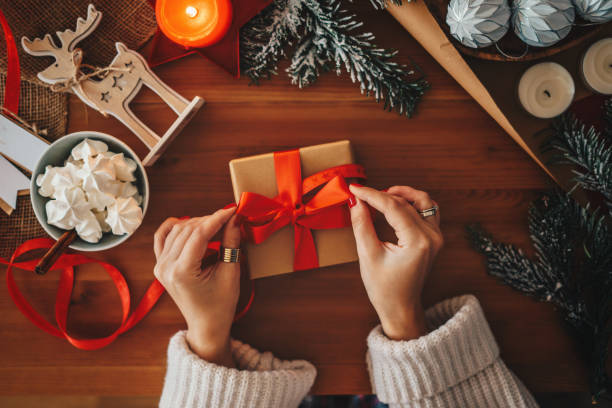 woman wrapping christmas gifts, overhead shot - avvolto foto e immagini stock