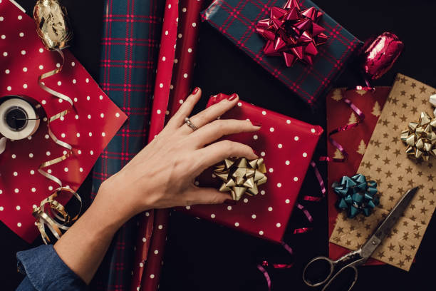 Woman wrapping christmas gifts presents photo taken from above overhead Woman wrapping christmas gifts presents photo taken from above overhead Hands wrapping paper bows. Table top shot taken directly above wrapping stock pictures, royalty-free photos & images