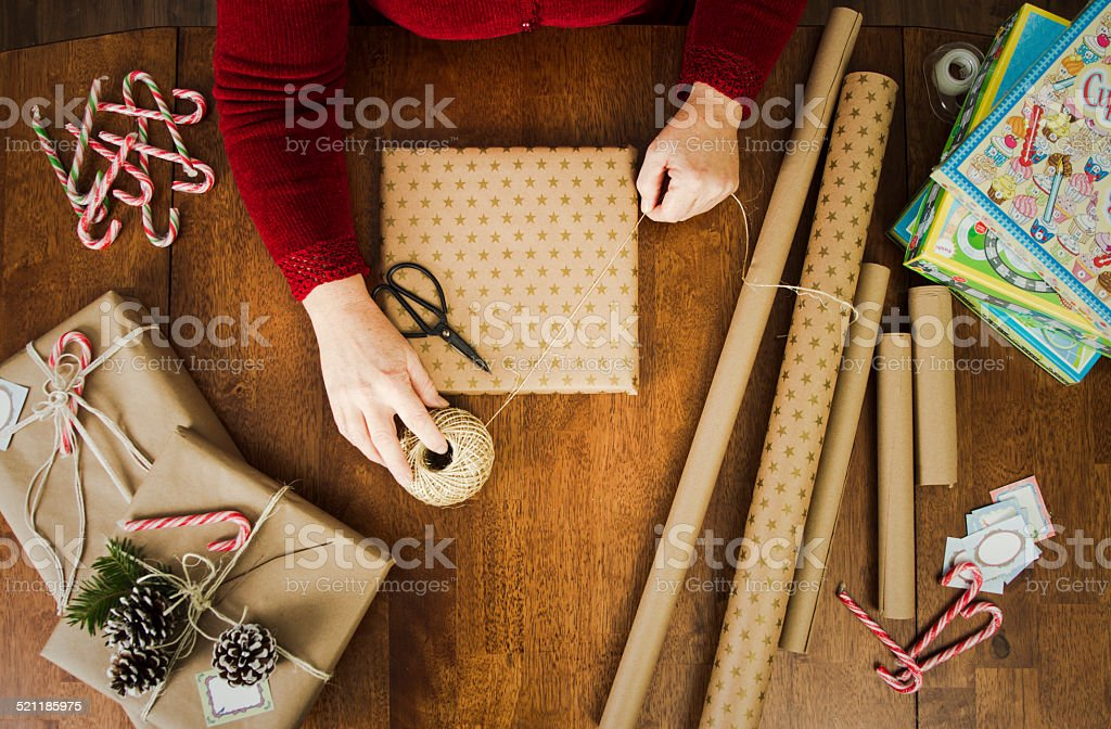 Woman Wrapping Christmas Gifts With Brown Paper & twine stock photo