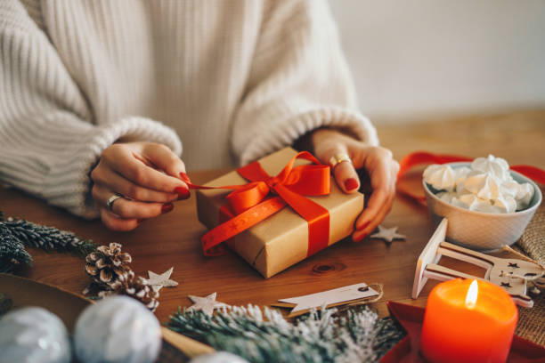 Woman wrapping Christmas presents at home Woman wrapping Christmas gifts wrapping stock pictures, royalty-free photos & images