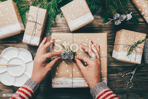 Woman´s hands wrapping Christmas presents on brown paper decorated with painted snow, fir branches and pinecones on a rustic wooden board. Top view