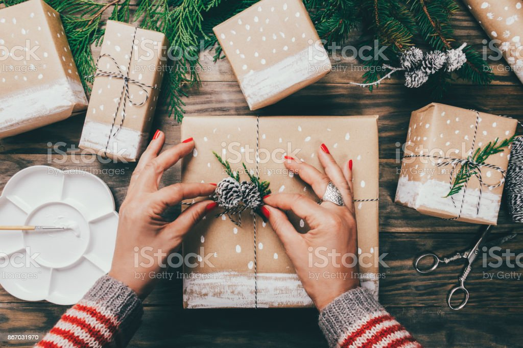 Woman wrapping Christmas presents in a crafty way stock photo